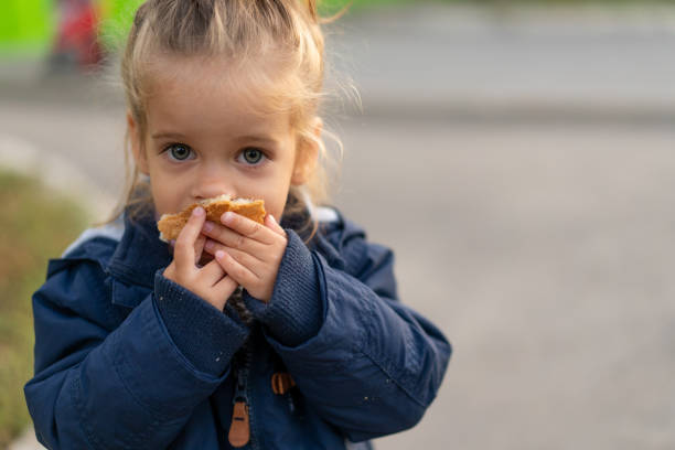 A beautiful little Caucasian girl with blond hair and eating bread eagerly with her hands looks at the camera with sad eyes A beautiful little Caucasian girl with blond hair and eating bread eagerly with her hands looks at the camera with sad eyes, an abandoned child and hungry. hungry stock pictures, royalty-free photos & images