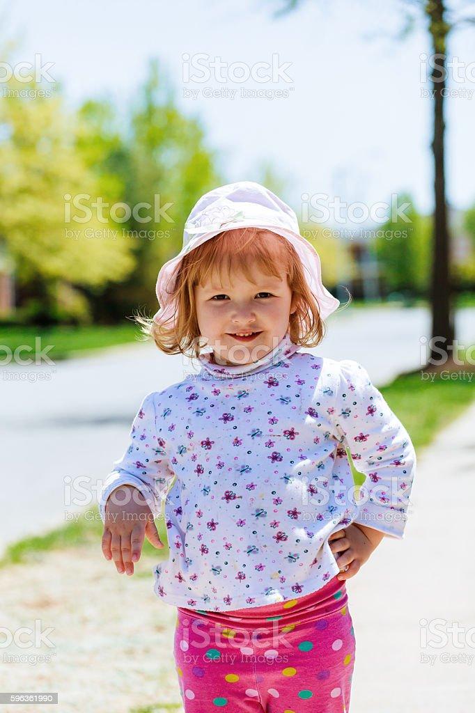 Beautiful little girl blowing dandelion on green meadow royalty-free stock photo