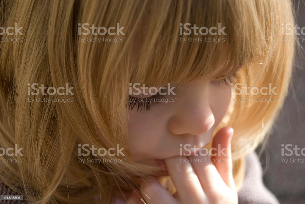 Beautiful little girl deep in thought stock photo