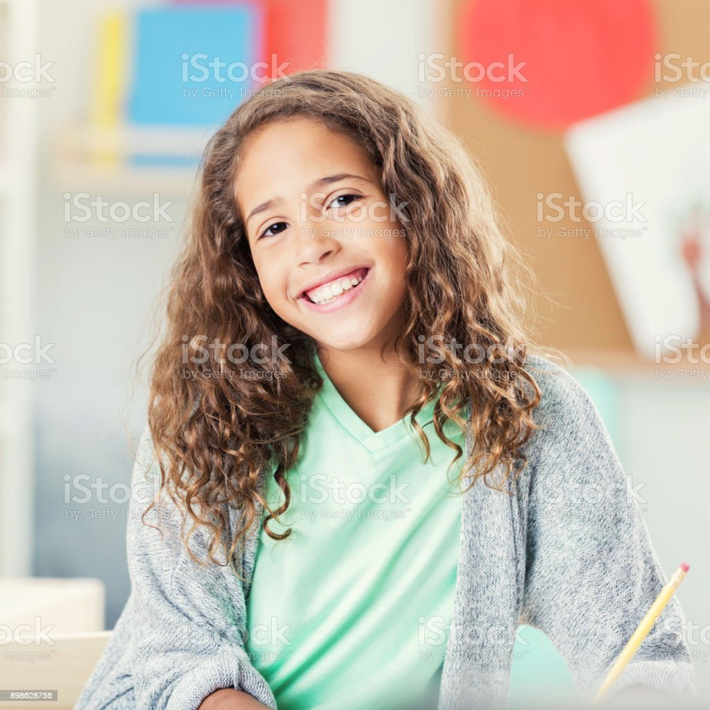 Beautiful little girl finishes homework during after school program stock photo