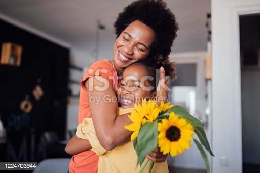 Little African American girl gifting her mother flowers for Mother's Day, making her feel special