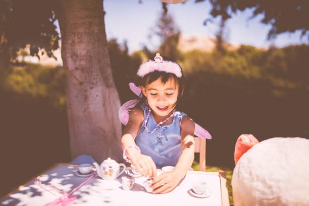 wunderschönes kleines mädchen mit einer tee-party im garten - sommerfest kindergarten stock-fotos und bilder