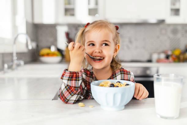 hermosa niña que desayuna con cereales, leche y arándanos en la cocina - desayuno fotografías e imágenes de stock