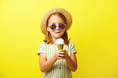 Beautiful little girl holding an ice cream and going to eat it, licking her lips, dressed in a summer dress, straw hat and sunglasses, standing on yellow isolated background.