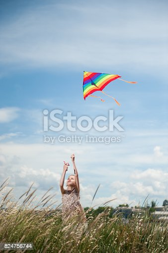 istock beautiful little girl holding flying kite in the field on summer sunny day 824756744