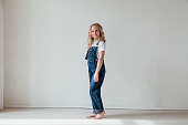little girl in denim jumpsuit played in white room