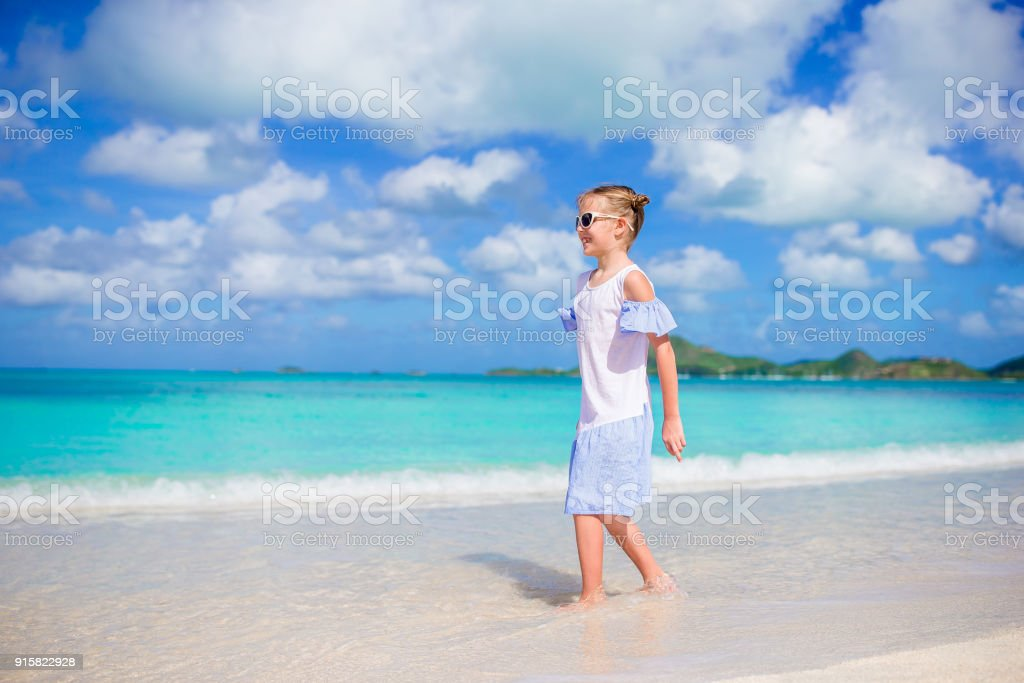 1ca943d943 Beautiful little girl in dress at beach having fun. Happy girl enjoy summer  vacation background the blue sky and turquoise water in the sea on  caribbean ...
