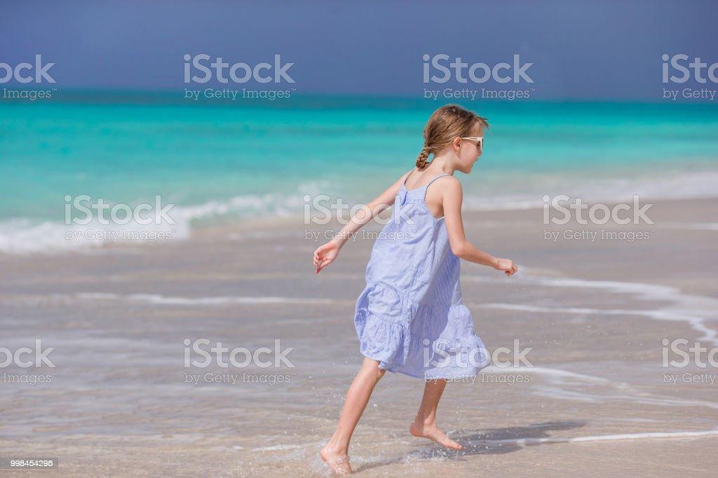 b3b88154fa Beautiful Little Girl In Dress At Beach Having Fun Stock Photo ...