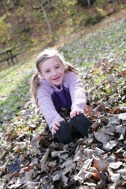 """Beautiful LIttle Girl in Leaves """"Beautiful little girl sitting in leaves.Shot with Canon 1Ds, Mark II, shallow depth of field, copy space available."""" touching toes stock pictures, royalty-free photos & images"""