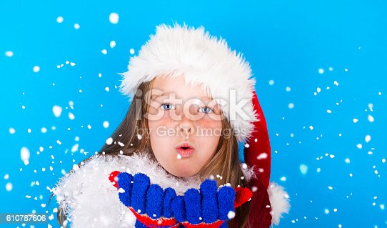 istock Beautiful little girl in Santa Claus hat blowing snowflakes 610787606