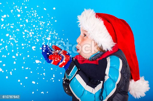 istock Beautiful little girl in Santa Claus hat blowing snowflakes 610787642