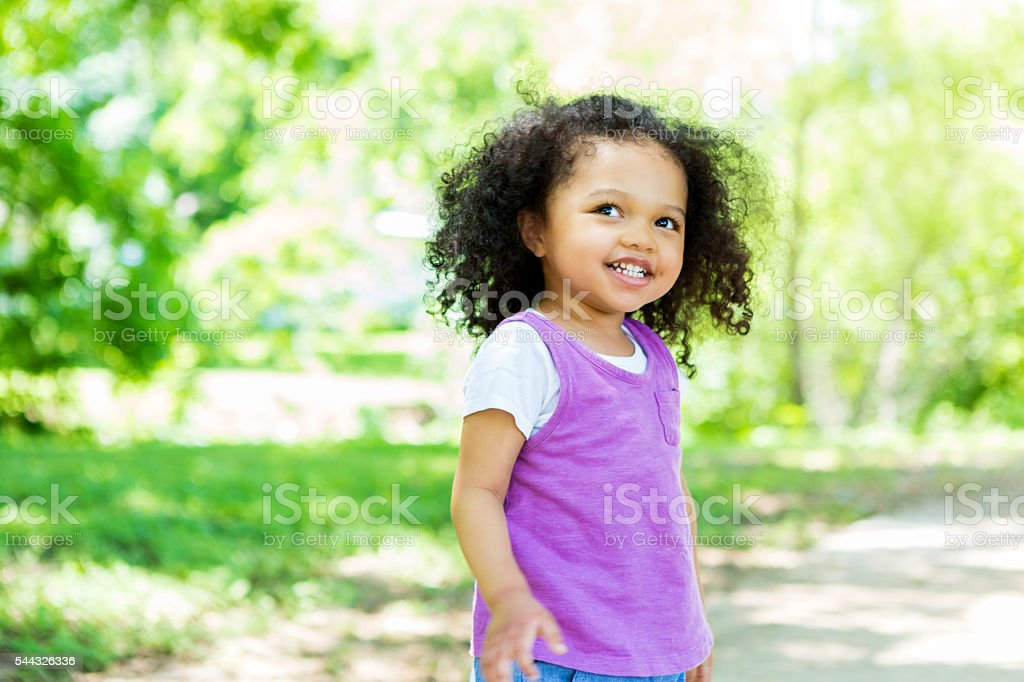 Beautiful little girl in the park on a sunny day stock photo