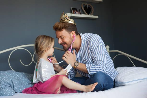 La hermosa niña está jugando a los doctores con su padre - foto de stock