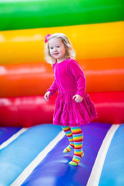 schöne kleine mädchen springen und auf und ab springen - sommerfest kindergarten stock-fotos und bilder