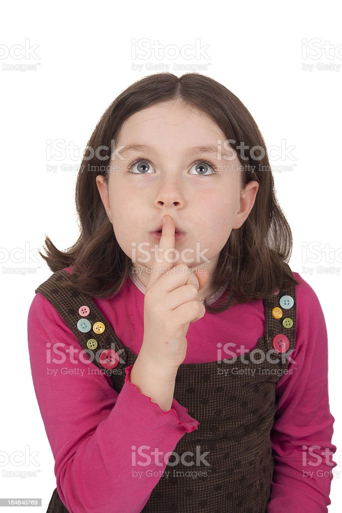 Beautiful little girl looking up and gesturing silence stock photo