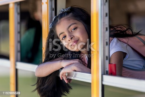 Elementary age girl looks out of a school bus window as the bus arrives at an elementary school.
