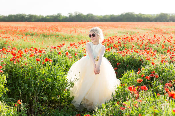 beautiful little girl model in a field of poppies, childhood, happiness, fashion, children, nature and summer flowers concept - smiling girlie in white fancy dress posing on poppy field, sunglasses - charming stock photos and pictures