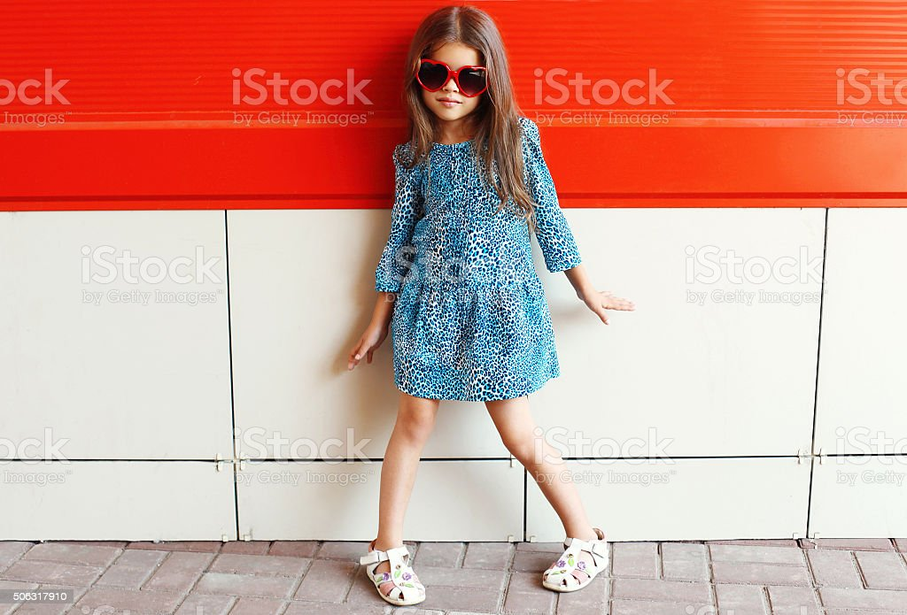 Beautiful little girl model wearing a leopard dress and sunglass stock photo
