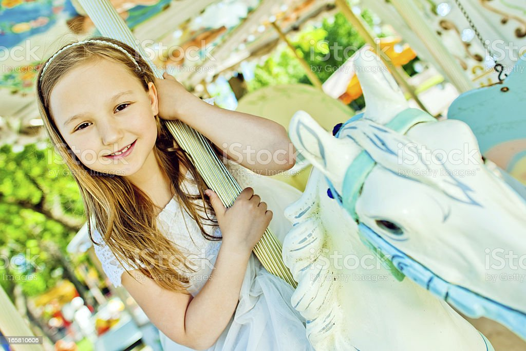 Beautiful little girl on a retro carousel ride royalty-free stock photo
