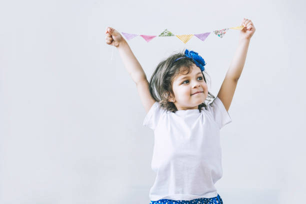 Beautiful little girl on white background with festive flags stock photo