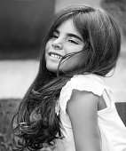 Fashion black and white photo of a beautiful little girl having fun in the park, closeup on happy face, model with long nice hair