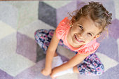Little beautiful girl sitting on carpet, looking at camera and playing with a smile.