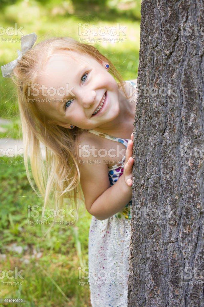 Beautiful Little Girl Playing Peek-A-Boo A beautiful 5 year old girl laughing as she plays peek-a-boo around a tree. 4-5 Years Stock Photo