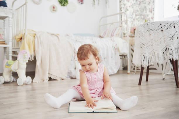 wunderschönes kleines mädchen spielen spielzeug. blauäugige blondine. weißer stuhl. kinderzimmer. glückliches kleines mädchen porträt. kindheit-konzept - himmelbett baby stock-fotos und bilder