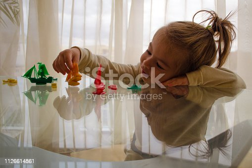 istock beautiful little girl playing with boats on a glass table 1126614861