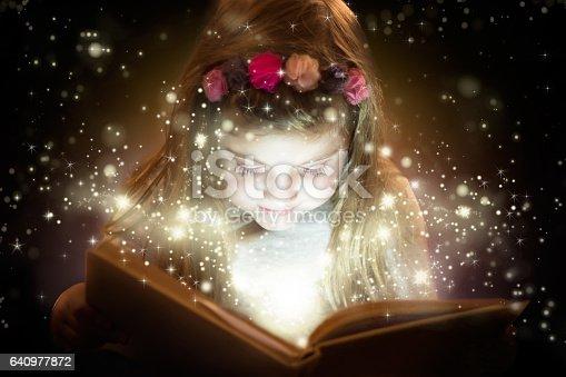 istock Beautiful little girl reading magic book 640977872