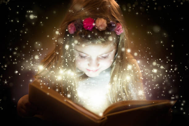Beautiful little girl reading magic book stock photo