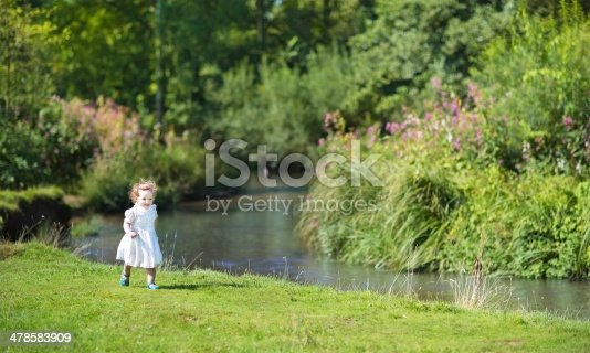 istock Beautiful little girl running at river shore on sunny day 478583909