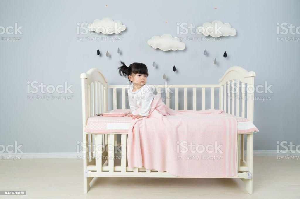 Beautiful Little Girl Sits On White Blanket In Her Bedroom Stock Photo Download Image Now Istock