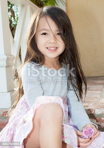 istock Beautiful little girl sitting on front porch 530763993