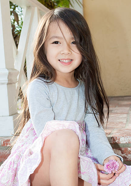 Beautiful little girl sitting on front porch stock photo