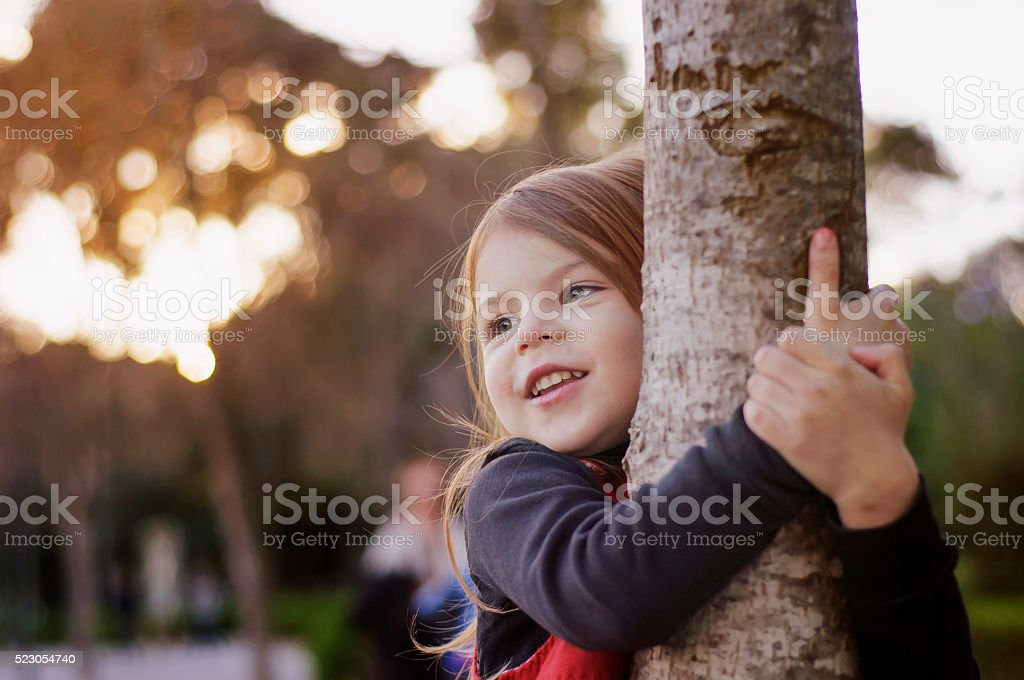 Beautiful little girl smiling hugging a tree trunk. stock photo