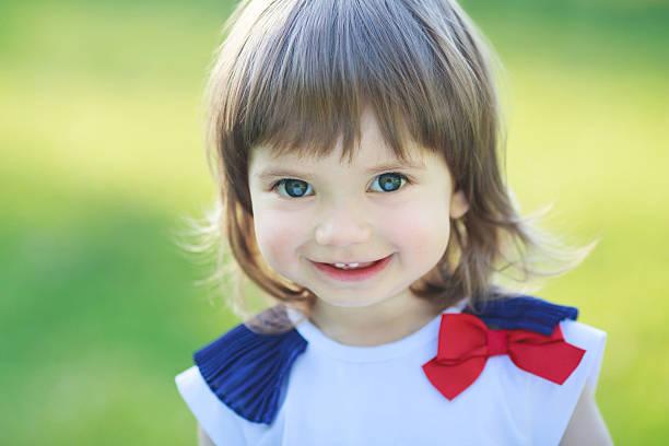 schönes kleines mädchen lächelt - drees und sommer stock-fotos und bilder