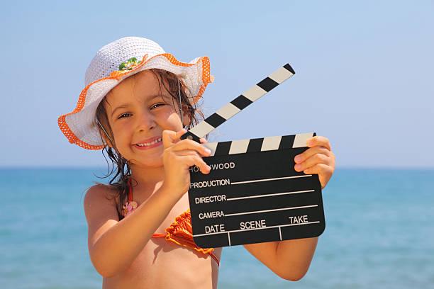 schönes kleines mädchen stehen am strand und hält schindel. - klappe hut stock-fotos und bilder