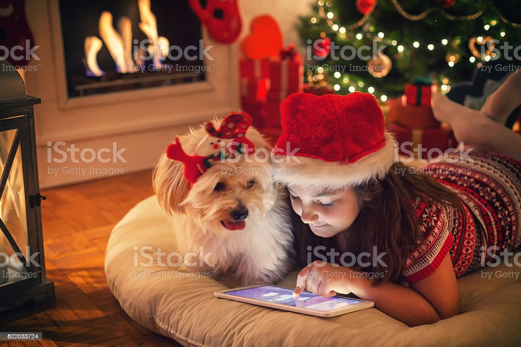 Beautiful little girl using digital tablet on Christmas night stock photo