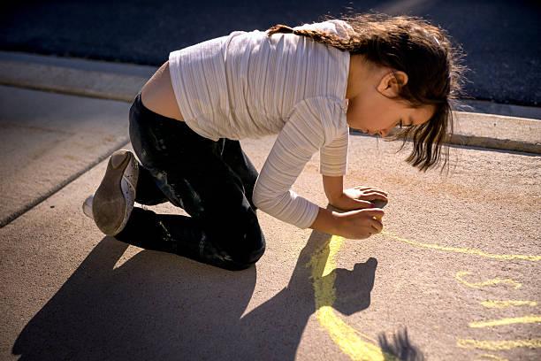 schönes kleines mädchen mit gehweg kreide - malerei schuhe stock-fotos und bilder