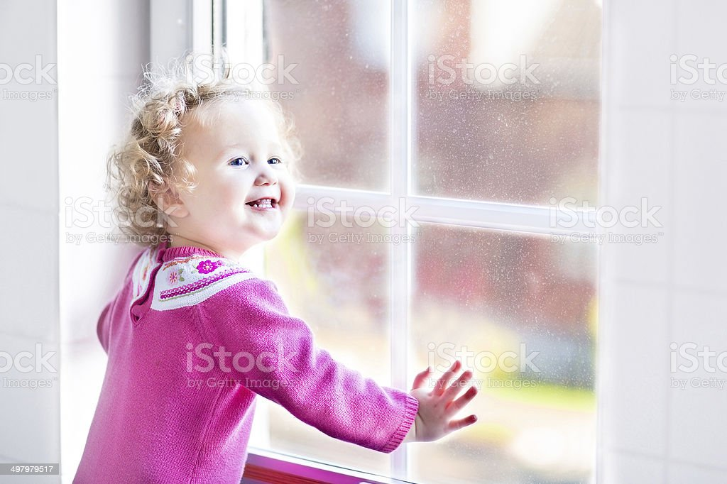 Beautiful little girl watching out of window with autumn trees royalty-free stock photo
