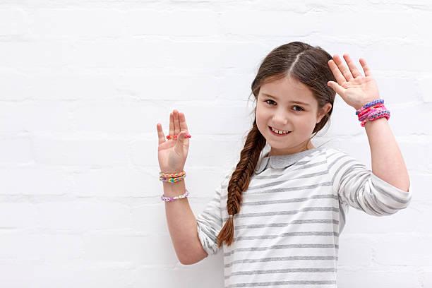 schöne kleine mädchen mit bunten webstuhl bands auf der suche glücklich - armband i gummi stock-fotos und bilder