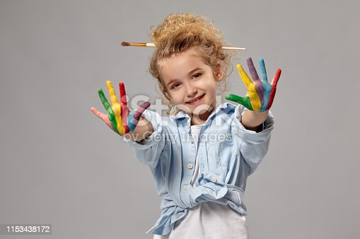 Lovely child having a brush in her chic curly blond hair, wearing in a blue shirt and white t-shirt. She is showing her painted fingers, looking at the camera and smiling, on a gray background.