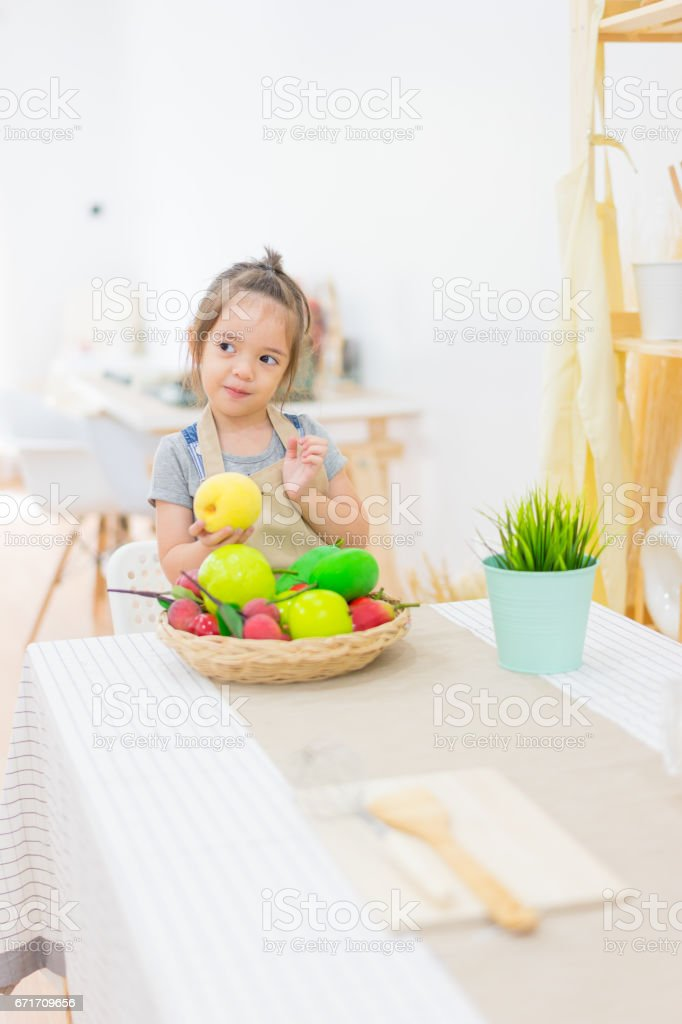 Beautiful little girl with fruits  in basket on kitchen table at house stock photo