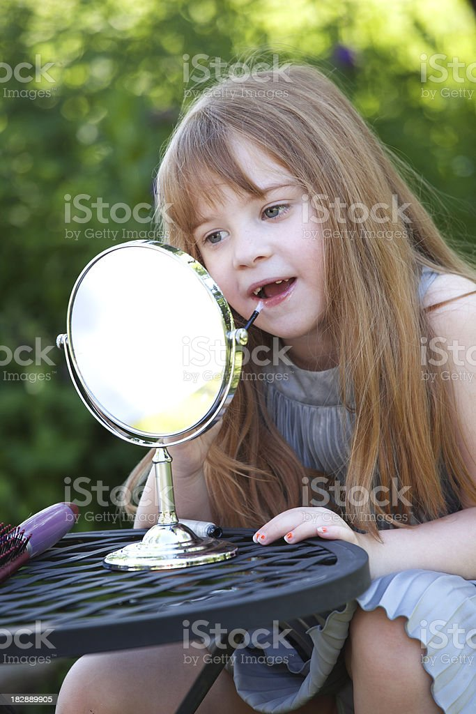 Beautiful Little Girl with Lipstick and Mirror stock photo
