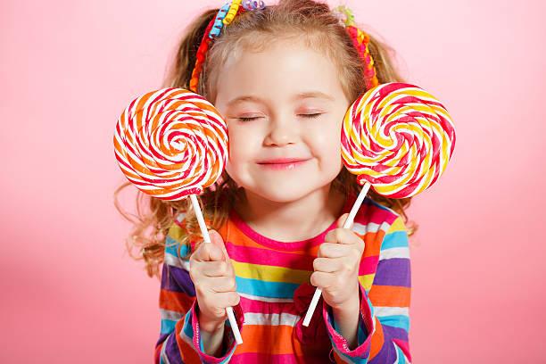 Beautiful little girl with lollipop stock photo
