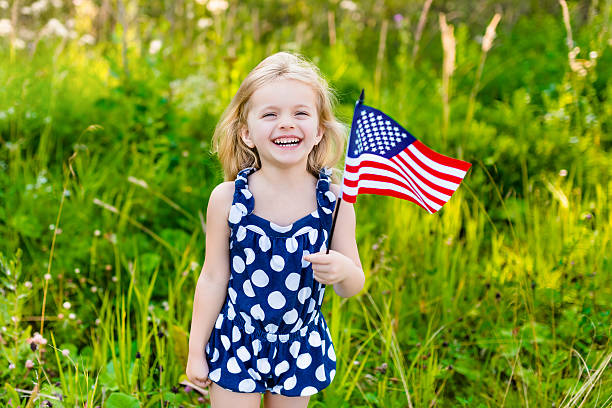Beautiful little girl with long blond hair with american flag stock photo