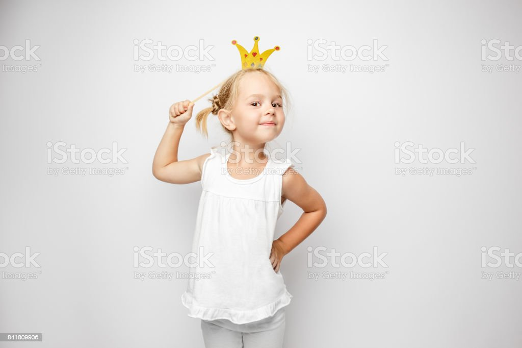 Beautiful little girl with paper crown posing on white backgroun stock photo