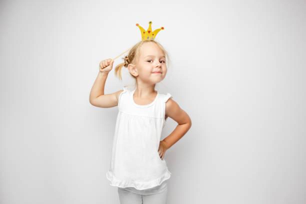 wunderschönes kleines mädchen mit papierkrone posiert auf weißen zeitmessung - kinderparty spiele stock-fotos und bilder