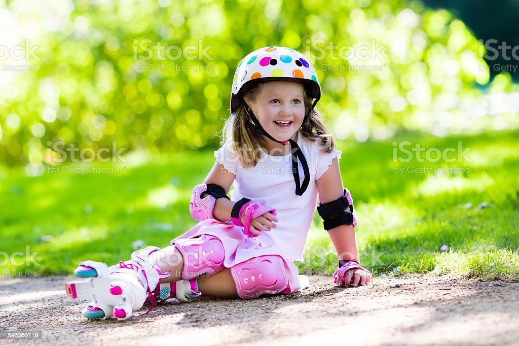 Beautiful little girl with roller skate shoes in a park royalty-free stock photo